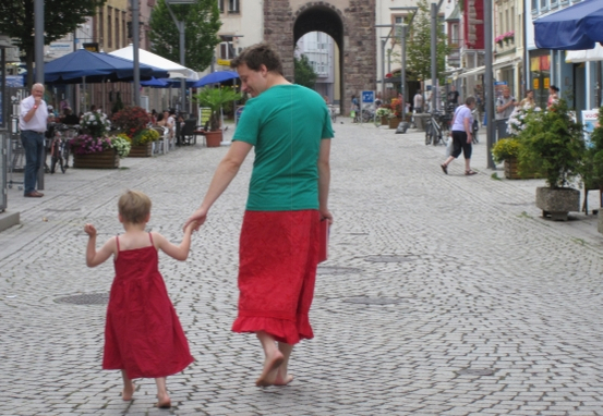 A man wearing a red skirt and teal t-shirt holds hands with a small boy wearing red dress. Their backs are to the camera, but the man's head is turned to show him smiling at the child.